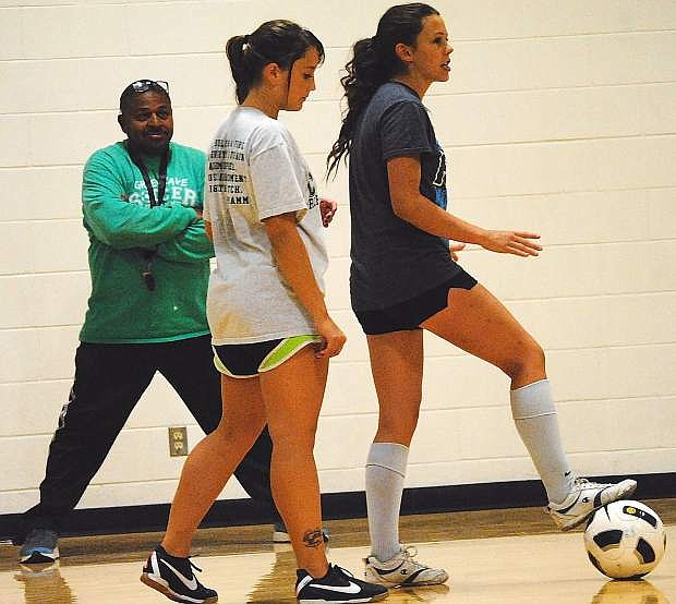 Fallon girls soccer coach Kelly Spicer, left, watches as senior Monica Mills, right, outlines a drill with Haley Sanches during Monday's practice.