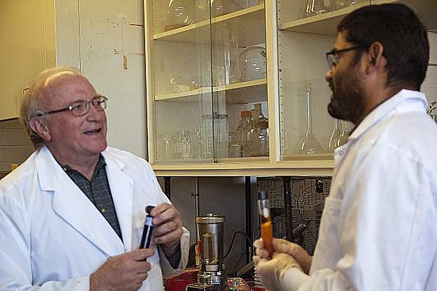Glenn Miller and Bishnu Neupane holding the final biofuel product based on the gumweed plant. The fluids in the tubes have been diluted at different levels and are being examined in the labs at the Applied research Facility at the University of Nevada main campus.