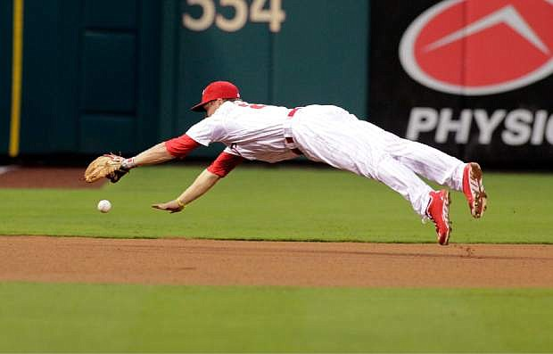 Philadelphia Phillies' Cody Asche has trouble fielding a double hit by San Francisco Giants' Buster Posey in the fourth inning of a baseball game, Thursday, Aug. 1, 2013, in Philadelphia. (AP Photo/H. Rumph Jr)