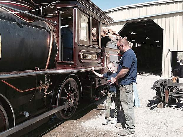 Corvin Dolan watches his dad, Morton Dolan, make last-minute checks on the Glenbrook steam locomotive.