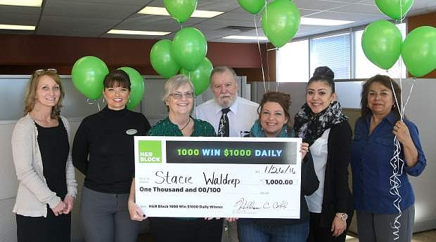 """H&R Block is putting the """"fun"""" back in refund season. Carson City resident Stacie Waldrep, third from right, was a winner in the H&R Block 1,000 Win $1,000 Daily Sweepstakes. The staff, l-r, Tara Whitney, Tonya Wood, Cathy McClure, John Osko, Neira Alejandra Araiza and Tencha Sprock of the H&R Block office located at Mills Park Center presented the $1,000 check to Waldrep on Tuesday."""