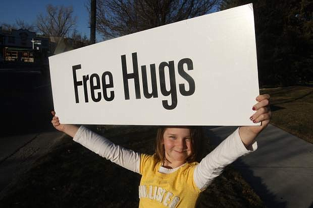 Chloe Clark, 8, displays a sign at the Happiness Sprinkling Project on Monday in front of the Legislature building.