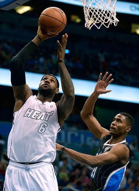 Miami Heat forward LeBron James (6) shoots in front of Orlando Magic forward Maurice Harkless during the first half of an NBA basketball game in Orlando, Fla., Monday, March 25, 2013. (AP Photo/Phelan M. Ebenhack)