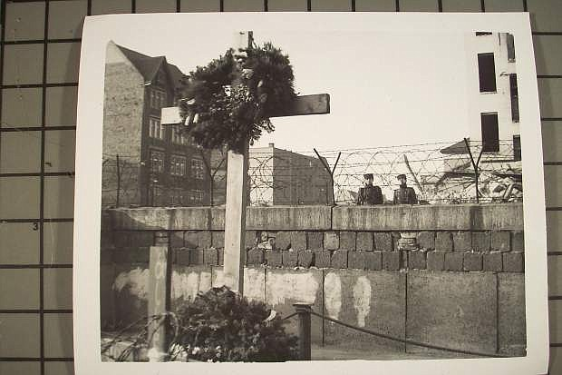 This photo, taken in the early 1960s from West Berlin by LVN columnist David Henley, shows East Berlin border policemen on the East Berlin side of the Berlin Wall looking at a West German memorial honoring an East Berliner who was shot to death attempting to scale the Wall to freedom in West Berlin.