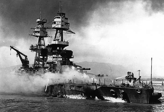 Navy fireboats battle flames aboard the USS Nevada after it received several direct hits from Japanese torpedo planes on Dec. 7, 1941.
