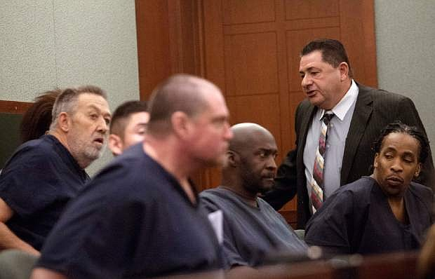 Defense attorney Frederick Santacroce, top right, speaks with former nurse anesthetist Ronald Lakeman, left, a former employee of Dipak Desai's Endoscopy Clinic of Southern Nevada, center, at a hearing at the Regional Justice Center in Las Vegas Thursday, Sep. 5, 2013.  Sentencing has been postponed until Oct. 24 for the former Las Vegas endoscopy clinic owner and a former employee facing prison following their criminal convictions in July in a 2007 hepatitis C outbreak. Clark County District Court Judge Valerie Adair said Thursday, Sept. 5, 2013,  she couldn't sentence Dipak Desai and former nurse-anesthetist Ronald Lakeman, without a presentencing report from state officials. The 63-year-old Desai and 66-year-old Lakeman face what could be decades in prison after being found guilty July 1.