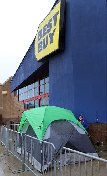"Cassie DeMontigny gets ready to spend the night outside the Best Buy Wednesday, Nov. 27, 2013 in Concord, N.H. DeMontigny is bypassing the Thanksgiving diner to be first in line when the store opens Thursday at 5:00 pm searching for a TV, an iPad 2 and ""maybe a camera."" (AP Photo/Jim Cole)"