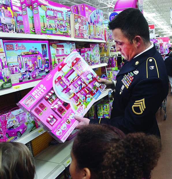 Army National Guard Staff Sgt. Jacob Roberts helps children as they picked out toys during the 9th annual Holiday with a Hero event at Walmart on Tuesday.