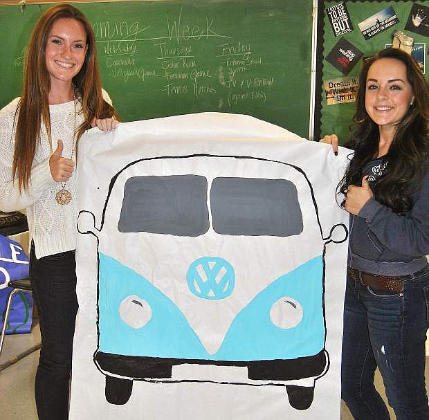 Jordyn Rodgers and Nichole Mariezcurrena, right, hold up one of the banners Student Council members created for Homecoming week's Coachella Day.