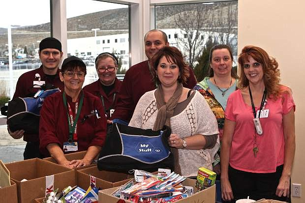 Front, from left: Clara Eskew, Kayleen Fogleman, Lorri Baker (back row) Mark Lisowski, Patty Hollowell, James Reyes and Leigh Alvorson volunteer to stuff duffle bags full of clothing and other household needs for displaced kids during the holidays at Carson-Tahoe Medical Center on Friday.