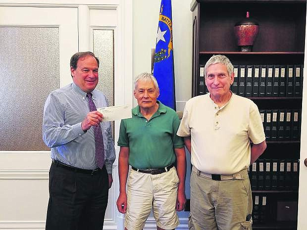 Treasurer Dan Schwartz hands Stewart Nelson and his business partner Michael Levitt a check from the Unclaimed Property Fund.