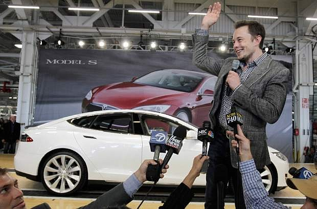 "FILE - In this June 22, 2012 file photo, Tesla CEO Elon Musk waves during a rally at the Tesla factory in Fremont, Calif. Musk on Monday, Aug. 12, 2013 unveiled a concept for a transport system he says would make the nearly 400-mile trip in half the time it takes an airplane. The ""Hyperloop"" system would use a large tube. Inside, capsules would float on air, traveling at over 700 miles per hour. (AP Photo/Paul Sakuma, File)"