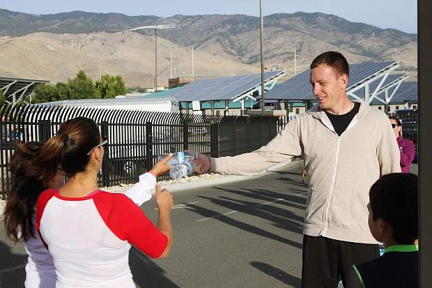 John Fansler passes out water at the finish line at the National Guard base after the IHOP Rememberance Run Sunday in Carson City.