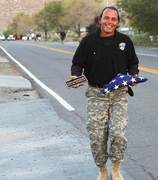 Ken Curtzwiler carries a flag and plaque in memory of Nevada National Guard Sgt 1st Class Miranda McElhiney on Saturday.