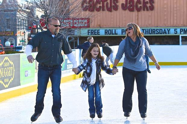 Robert, Ashley, 10, and Iria Williams from Valley Springs, California enjoy opening day at the Arlington Square ice rink on Friday. The Arlington Square Ice Rink can be reached at 775-283-7429 for hours and pricing information.