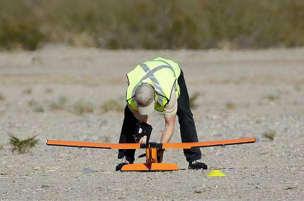 Scott Carrigan of Sensurion Aerospace picks up the company's Magpie commercial drone after it crashed during launch Friday, Dec. 19, 2014, near Boulder City, Nev. The attempted flight was at an event to announce the FAA's first issuance of an unmanned aerial systems test site special airworthiness certificate. (AP Photo/John Locher)
