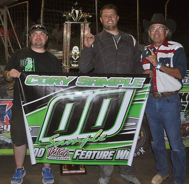 From the left: P.J. Risso, Cory Sample and Announcer Davey Munoz pose for a photo celebrating Sample winning Iron Man and his 100th IMCA event.