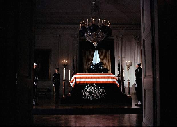 "FILE - In this Saturday, Nov. 23, 1963 file photo, the flag-draped casket of President John F. Kennedy lies in state in the East Room of the White House in Washington. ""Jackie Kennedy sent word that she wanted the East Room, where the president would lie in state, to look as it did when Lincoln's body lay there,"" remembers Richard Goodwin, a speechwriter and adviser to the administration. He and others went to work. Someone was sent to the Library of Congress for a sketch and a newspaper description from Lincoln's time; artists and upholsterers were called in, and black crepe was carefully hung. ""In the midst of all these activities we would alternately break down in tears,"" Goodwin says. (AP Photo)"