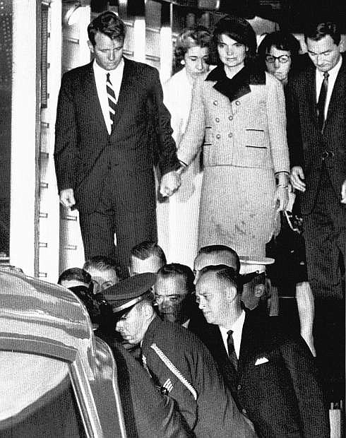 FILE - In this Friday, Nov. 22, 1963 file photo, Jacqueline Kennedy, with bloodstains on her clothes, holds hands with her brother-in-law, Attorney General Robert Kennedy, as the coffin carrying the body of President John F. Kennedy is placed in an ambulance after arriving at Andrews Air Force Base, Md. near Washington. President Kennedy was assassinated earlier that afternoon in Dallas. (AP Photo)