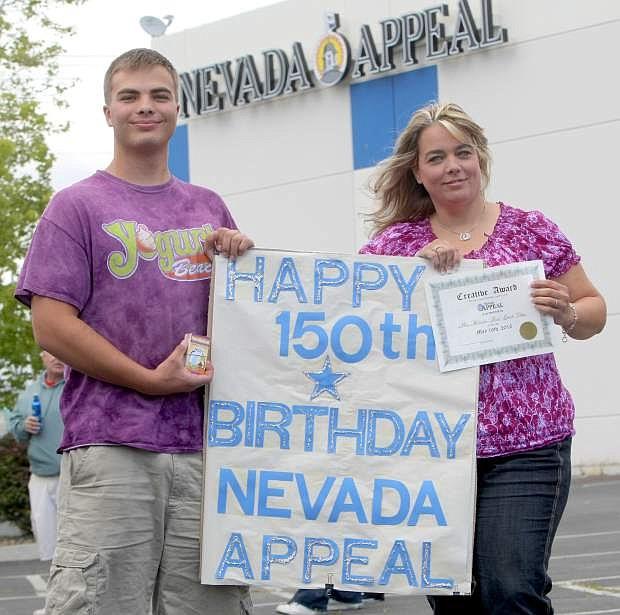 Representatives from Yogurt Beach, Logan Clark and Teresa Morrow, display the winning Newspapers in Education poster winner.