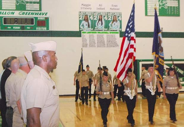 Command Master Chief Bobby Anderson from Naval Air Station salutes the Vhurchill County High School Junior ROTC guard color during pass and review on Friday.
