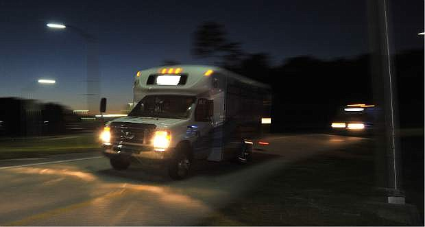 Shuttles used to move people out of Jacksonville International Airport drive by Tuesday, Oct. 1, 2013, in Jacksonville, Fla. The airport was evacuated after authorities found two suspicious packages. (AP Photo/The Florida Times-Union, Bruce Lipsky)