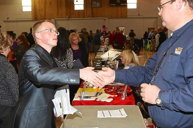 Thomas Stair of Carson City shakes hands with ESI Security's Peter Eastman Friday at the Community Center during the job fair.