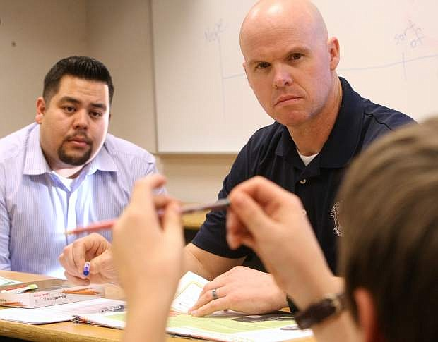 Juvenile Probation Officers Matt Clapham, foreground, and Mike Rapisora give their full attention to a participant telling a story about school at the Forward Thinking Family program on Tuesday.