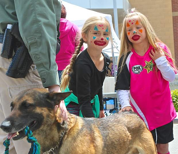 Hailee Satterwhite, 8, and Addi Paxton, 7, give Darren Riggin's K9 'Tarzan' some pets during the Cops and Kids event earlier this year.
