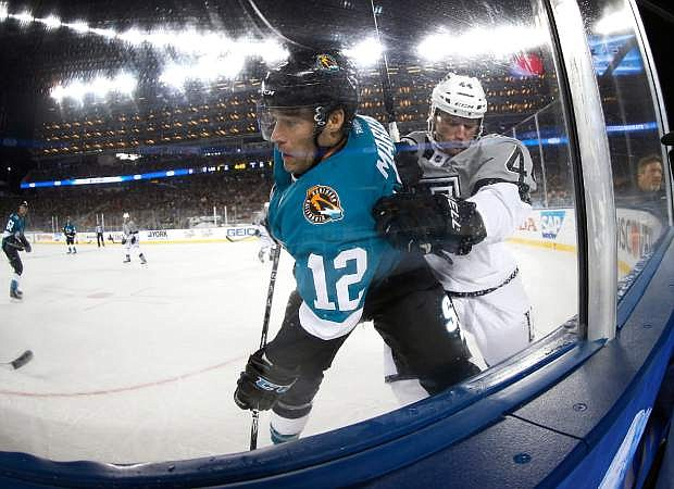 San Jose Sharks center Patrick Marleau (12) is checked into the boards by Los Angeles Kings defenseman Robyn Regehr (44) during the third period of an NHL hockey game Saturday, Feb. 21, 2015, in Santa Clara, Calif. The Kings won 2-1. (AP Photo/Tony Avelar)
