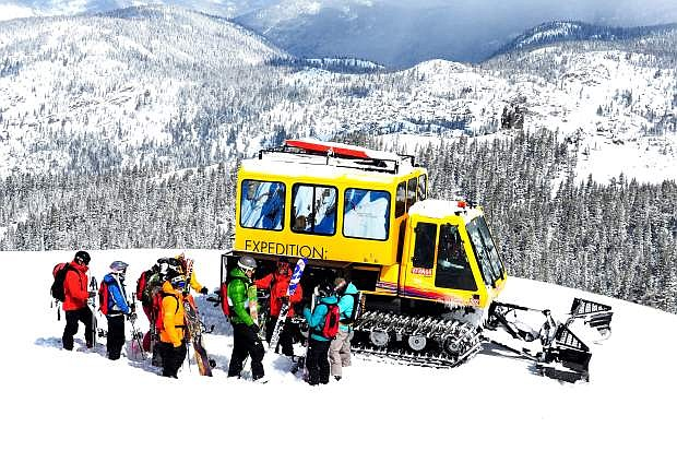 A group of skiers and snowboarders stand in front of a snow cat on a powder day while cat skiing at Kirkwood Mountain Resort, California.