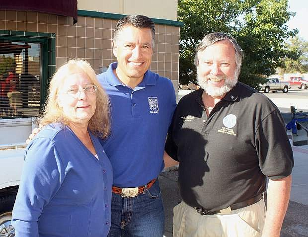 Jennie Mader, left, and Tom Millham, right, Kiwanis District Governor for 2010-2011, pose with Gov. Brian Sandoval before he eats breakfast.