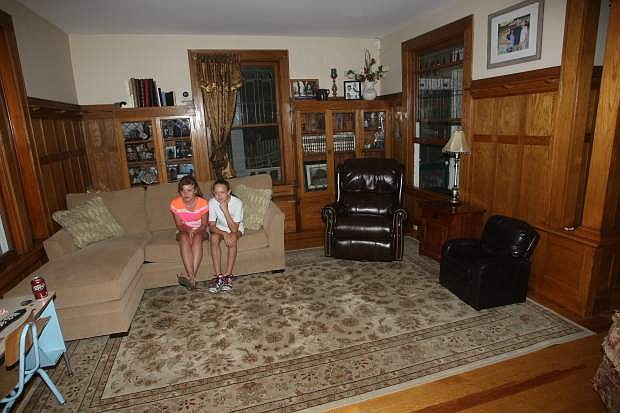 Brooke Robinson, 12, and Katie Fralick, 11, sit on the couch in the living room of the century old Krebs-Peterson mansion on Saturday.