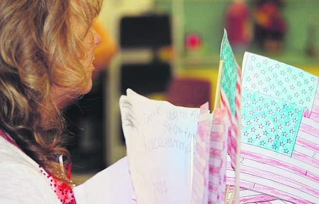 Lahontan Elementary School Kieran Kalt teacher holds handmade American flags and scripts.