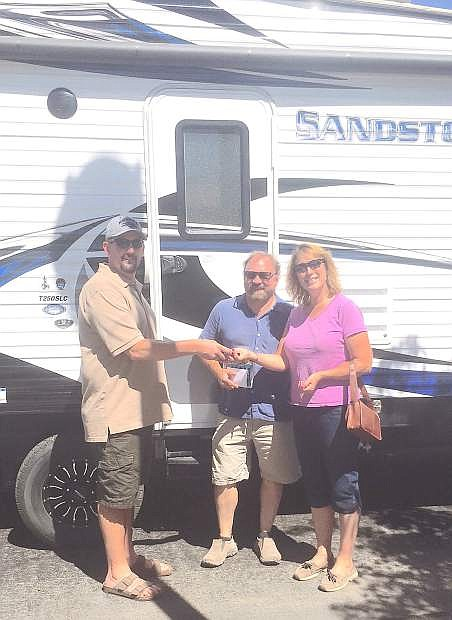 Ryan Swirczek hands the keys to the 35-foot Toy Hauler trailer to Gary and Katherine Mills, this year's Live Local Fallon grand-prize winners.