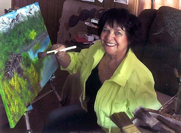 Rosie Laird paints a landscape in oil. Laird is volunteering with 4-H to offer art classes to children ages 9-11.
