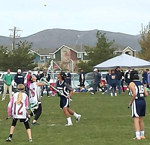 Oasis girls lacrosse players Alanna Muir and Meeka Erwin watch as the ball flies through the air during their game against the Reno Wildfires on Saturday. Oasis won its first-ever girls game.