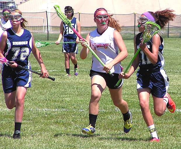 Madie Whitaker, right, and Emily Giovanetti run toward the goal during the Bighorns' 9-8 loss to Reno. Whitaker scored all eight goals for Oasis.