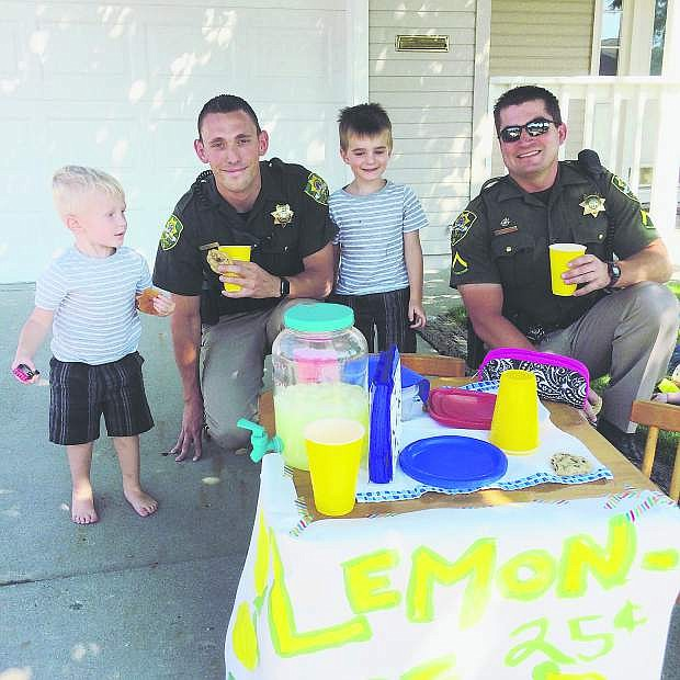 Carson City brothers Joseph and Owen Pruyt are visited by Carson City Deputies Cody Bindley and Matt Smith at their lemonade stand Monday afternoon.