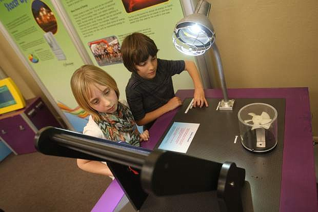 Mira Caraway, 11, and Will Contine, 10, experiment with solar energy at the Discover Tech: Engineers Make a World of Difference exhibit at the Carson City Library.