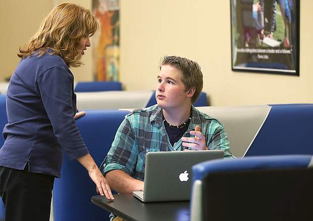 Out of School Time Coordinator Molly Walt talks with Carson High student Sam Wilson, 16, in the Digitorium at the Carson City Library in Carson City, Nev., on Thursday, May 27, 2015. Wilson used the free library wi-fi to work on his resume to help get a job.