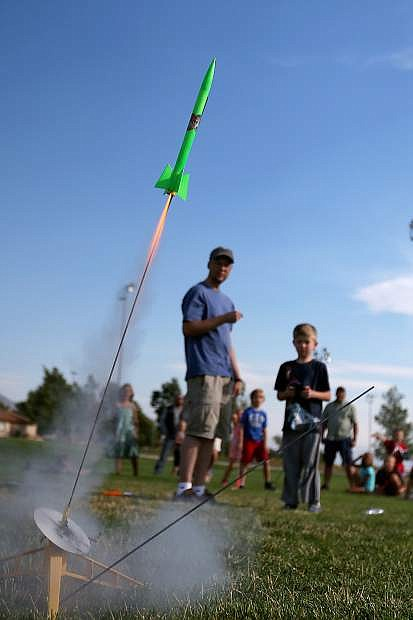 Kevin Clifford, with the Reno Rocketry Club, helps Hayden Brundage, 6, launch a rocket during a Carson City Library Summer Reading Program event at Edmonds Sports Complex on Saturday. Wild Things, Inc. will be at the library 5:30 and 6:30 p.m. today, bringing a  live kangaroo and alligtor to the Digitorium.