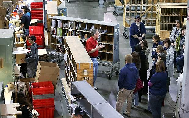 Don Finch, director of operations at Baker and Taylor, center, gives Carson City Library staff members a tour of the 250,000 square foot book distribution center in Reno on Dec. 19. The tour is part of ongoing staff training sessions that help the Carson City Library operate more efficiently and improve customer service.
