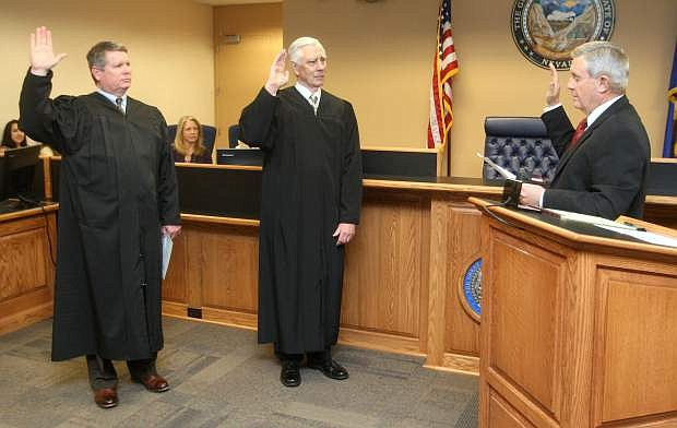 Nevada Chief Justice James Hardesty, right, swears in District Court Judge James Wilson and District Court Judge James Russell on Monday.