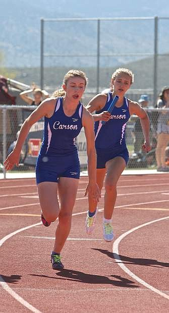 Junior Athena Favero prepares to give the stick to sophomore Valerie-Sue Meyer during the girls 4x200-meter relay in which Carson set a school record at 1:44.33.