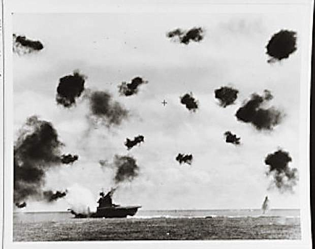 USS Yorktown (CV 5) is hit on the port side, amidships, by a Japanese Type 91 aerial torpedo during the mid-afternoon attack by planes from the carrier Hiryu, June 4, 1942. Photographed from USS Pensacola (CA 24). Yorktown is heeling to port and is seen at a different aspect than in other views taken by Pensacola, indicating that this is the second of the two torpedo hits she received.