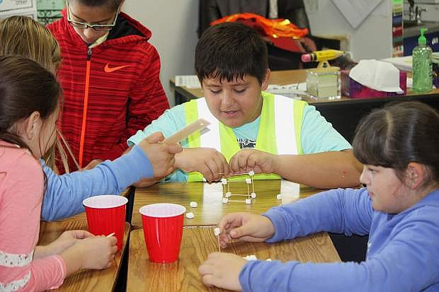 Mark Twain fourth-grader Brian Mendoza creates a marshmallow and toothpick mineshaft to represent what miners used to create.