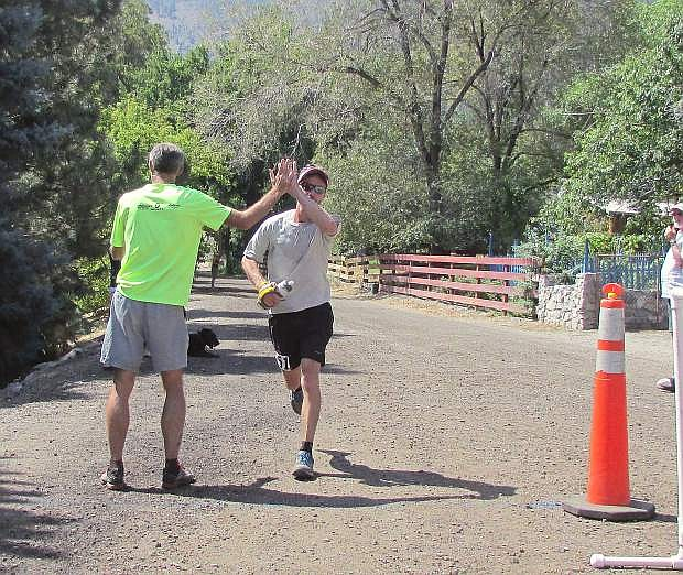 Paul Sweeney of Truckee receives a high-five at the finish line Saturday as he wins the second annual Genoa Peak Madathon.