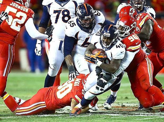 Chiefs linebacker Josh Mauga, on ground, and Jaye Howard bring down Denver running back Juwan Thompson during Kansas City's 29-16 loss on Sunday.