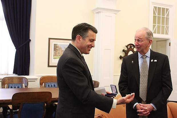 Gov. Sandoval admires the commemorative medallion presented by Bud Southard, right, of the U.S. Navy League, Carson City Council, and Mayor Bob Crowell.